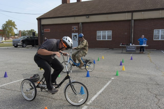 Brian Hill (left), Director, Warfighter Directorate, and Col. John Hall, Commander, U.S. Army Aberdeen Test Center (ATC), test their ability to ride a bicycle using goggles designed to replicate the effects of alcohol usage. The activity was one of several events at the annual ATC Safe Driving Roadeo, an event designed to highlight safe driving techniques. U.S. Army photo by U.S. Army Aberdeen Test Center