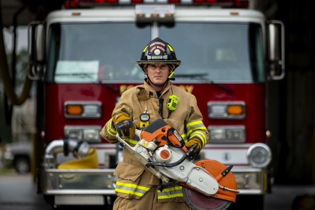 Brian Butzler, a firefighter with the Fort McCoy Fire Department, holds a K-12 Fire-Rescue Saw for a portrait after completing equipment checks and inspections at Station One located on Fort McCoy, Wisconsin, Aug. 12, 2019. Station One deploys fire engines, ambulances, command vehicles, and other response teams and equipment primarily within Fort McCoy's cantonment area. However, the FMFD also has a second station, which partners with local emergency response teams to serve Sparta and other nearby towns in Monroe County. (U.S. Army Reserve photo by Master Sgt. Michel Sauret)