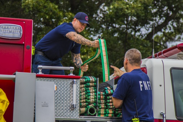 Fort McCoy Fire Department firefighters refold a water hose during routine training at Station One on Fort McCoy, Wisconsin, Aug. 12, 2019. The department operates two stations that serve the 60,000 acre Army installation and its surrounding cities through various capacities like emergency medical services, aircraft rescue and firefighting, search and rescue and more. (U.S. Army Reserve photo by Spc. Nicole Baker)