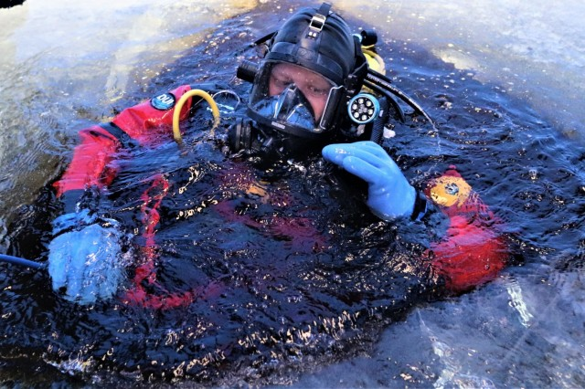 A firefighter wearing a full diving suit and related equipment dives into an open hole in the ice Feb. 6, 2019, at Big Sandy Lake on South Post at Fort McCoy, Wis. About a dozen firefighters with the Directorate of Emergency Services Fire Department practiced ice diving as part of the Fort McCoy dive team. Overall, the firefighters completed four days of training related to ice diving that also included classroom time and practice at the pool at Rumpel Fitness Center. Fort McCoy built the dive team capability eight years ago and the team has responded to real-world emergencies, including recently to an emergency in Sparta, Wis. (U.S. Army Photo by Scott T. Sturkol, Public Affairs Office, Fort McCoy, Wis.)