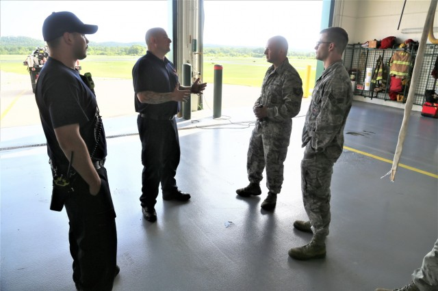Air Force firefighters supporting the Patriot North 2019 exercise talk with Fort McCoy firefighters July 16, 2019, at Station 2 of the Fort McCoy (Wis.) Fire Department during an exercise scenario. The National Guard Bureau exercise is designed for civilian emergency management and responders to work with military entities in the same manner they would during disasters. Patriot North provided Soldiers and Airmen with a chance to improve their skills to respond to a natural disaster and work with emergency management agencies. More than 700 civilians, volunteers, and National Guard Soldiers and Airmen from more than 20 states supported the 2019 exercise at Volk Field, Wis., and Fort McCoy. (U.S. Army Photo by Scott T. Sturkol, Public Affairs Office, Fort McCoy, Wis.)
