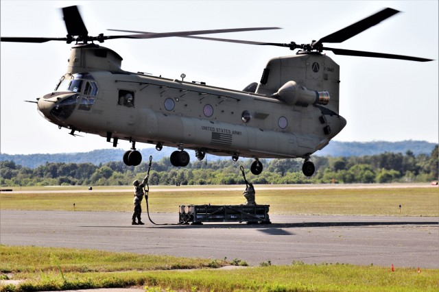 Students in the 89B Ammunition Supply Course connect a mock ammunition pallet to a CH-47 Chinook helicopter Aug. 1, 2019, as part of sling-load training at Sparta-Fort McCoy Airport at Fort McCoy, Wis. The Chinook and crew are from the 7th Battalion, 158th Aviation Regiment of New Century, Kansas. The Ammunition Supply Course, taught by the 13th Battalion, 100th Regiment at Fort McCoy, is a four-week course that provides training for Soldiers who are reclassifying to the 89B military occupational specialty. The sling-load training is one of the last major training events during the course. A sling load is used to transport munitions to remote locations or to expedite shipments in hostile locations. (U.S. Army Photo by Scott T. Sturkol, Public Affairs Office, Fort McCoy, Wis.)
