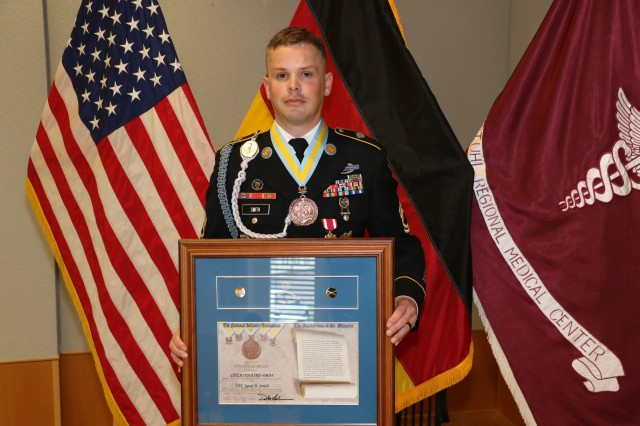 U.S. Army Sgt. 1st Class Jared Smith, an infantryman assigned as a platoon sergeant with the Medical Transient Detachment, Landstuhl Regional Medical Center, displays his awards and medal as a new inductee into the National Infantry Association's Order of Saint Maurice. The special honor is awarded to those who have significantly contributed to the infantry and stand out in the eyes of the their senior leaders, subordinates and peers. Smith is one of 10 infantrymen assigned to the MTD cadre -- the only combat arms Soldiers in the hospital's formation -- where he directly supports the medical treatment and disposition of wounded, injured and ill warfighters who come to LRMC from four different combatant commands.