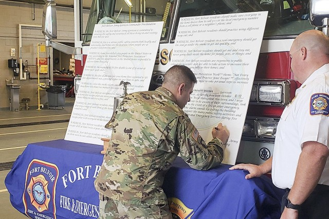 Col. Michael Greenberg, Fort Belvoir Garrison commander, signs the Fire Prevention Week proclamation at Fire Station 465 as Fire Chief Shane Crutcher looks on, Sept. 30. Fire Prevention Week, observed since 1922, is on record as the longest running public safety observance.