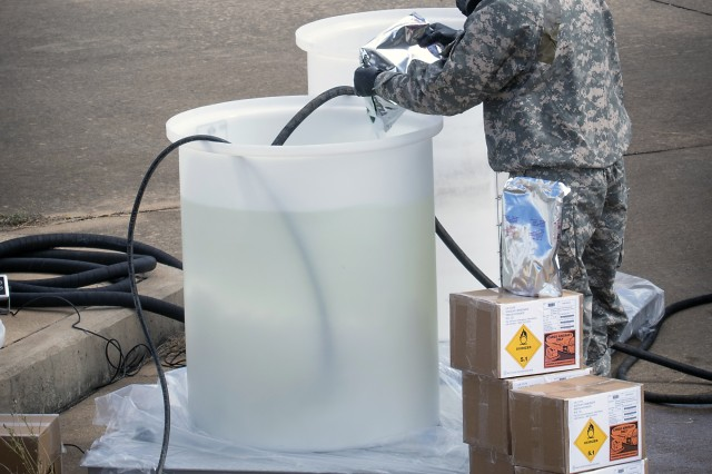 A 2nd Chemical Battalion Soldier adds Joint General Purpose Decontaminate for Hardened Military Equipment (JGPD-HME) to a container prior to mixing during operational testing at Fort Hood, Texas.