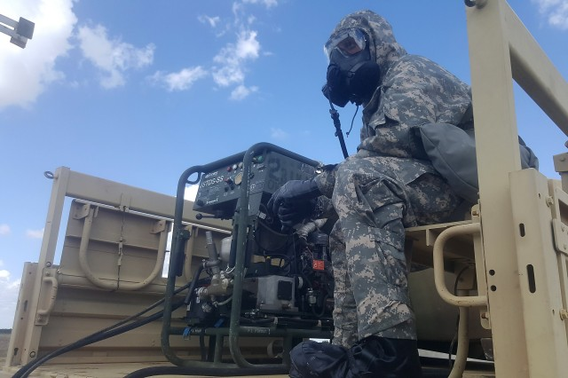 A 2nd Chemical Battalion Soldier operates the M26 decontamination apparatus with the Joint General Purpose Decontaminate for Hardened Military Equipment (JGPD-HME) during operational testing at Fort Hood, Texas.