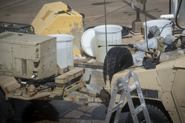 A 2nd Chemical Battalion Soldier operates the M26 decontamination apparatus with Joint General Purpose Decontaminate for Hardened Military Equipment (JGPD-HME) to decontaminate a generator during operational testing at Fort Hood, Texas.