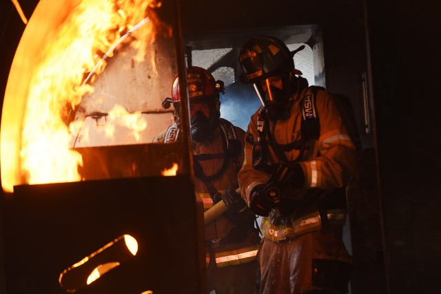 Fort Knox Garrison Commander Col. CJ King, Senior Enlisted Advisor Command Sgt. Maj. Garrick Griffin and Lt. Col. Samuel Meyer, Emergency Services director, donned firefighting gear and rode on firetrucks to the scene of a simulated aircraft crash as the sun set over the installation Oct. 9, 2019, to participate in annual firefighting training that has been hosted by Fort Knox Fire for the last 10 years. This year's weeklong event drew six fire departments and 20 firefighters.