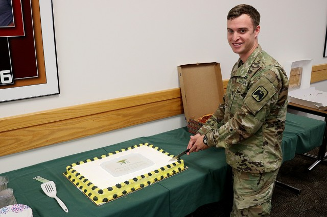 Capt. Zachary Quigg, a physician assistant with the 16th Combat Aviation Brigade, cut the cake for the commencement ceremony for the Interservice Physician Assistant Program and to acknowledge the start of PA week at Madigan Army Medical Center on Joint Base Lewis-McChord, Wash., on Oct. 7.