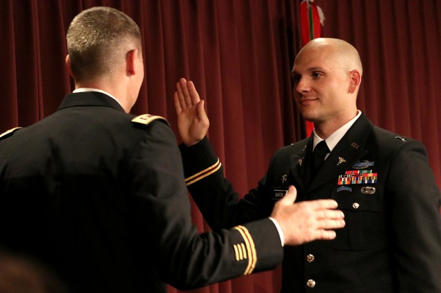 Maj. Nathan Williams, the coordinator for the Interservice Physician Assistant Program Phase II, administers the oath as Staff Sgt. Kieran Martin commissions as an officer in the Army Medical Specialist Corps after he graduated from the PA program. The commencement ceremony was held in Letterman Auditorium at Madigan Army Medical Center on Joint Base Lewis-McChord, Wash., on Oct. 7.
