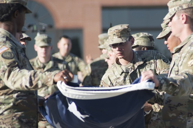 Soldiers from the Engineer Advanced Leader Course fold the flag during retreat Oct. 4 as part of the Maneuver Support Center of Excellence 20-year celebration.