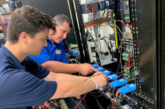 Alexander Johnston (left) and Dr. David Alan Wetz Jr. make a voltage measurement on a hybrid energy storage module at the University of Texas at Arlington.
