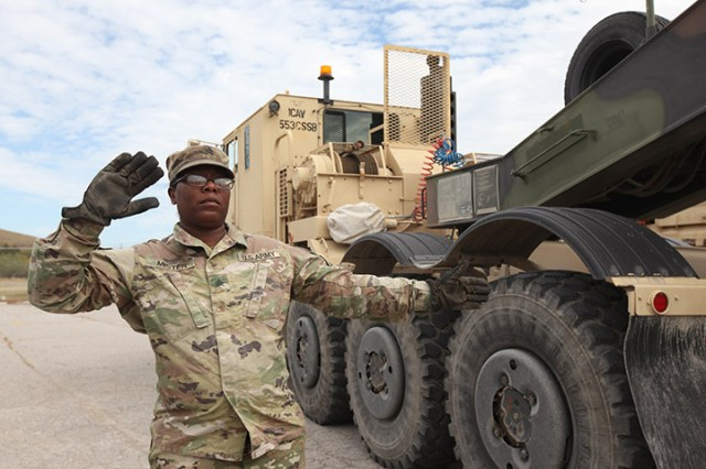 Sgt. Jeton Mister, 96th Transportation Company motor transport operator, guides a Heavy Equipment Transporter Systems vehicle into position Oct. 14, 2019, at Fort Sill. She was part of the 38 Soldiers from Fort Hood, Texas, who were at Fort Sill to get A Battery, 2nd Battalion, 2nd Field Artillery's howitzers to Texas for a training exercise.
