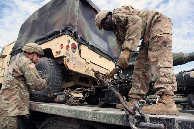 Sgt. Kordell Murphy and Spc. Daundre Geter-King, both of A/2-2nd FA, tie down an M119 howitzer to a semi-trailer bed Oct. 14, 2019, at Fort Sill. They were preparing to convoy to Fort Hood, Texas, as part of a deployment readiness exercise, and combined arms live-fire exercise.