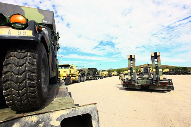 A line of Heavy Equipment Transporter Systems with loaded trailers sits in line at the Twin Peaks motor pool at Fort Sill, Oklahoma, Oct. 14, 2019. The trucks came from Fort Hood's 553rd Combat Sustainment Support Battalion, and their haul was from Fort Sill's A Battery, 2nd Battalion, 2nd Field Artillery.