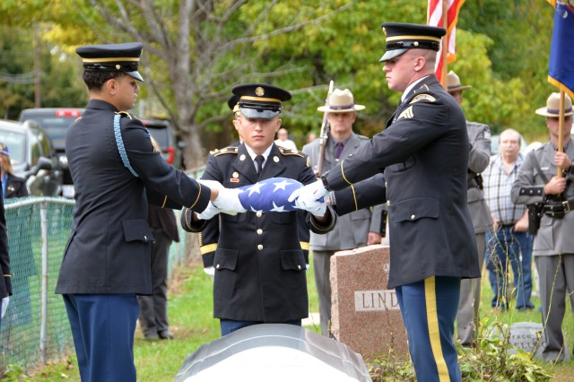 New York Army National Guard Sgt. Joshua Sanzo, right, and Pvt. Alexander Martinez, left, members of the New York Military Forces Honor Guard, fold the U.S. colors from the grave of Army Medal of Honor recipient Tech. Sgt. Francis S. Currey for Spc. Ryan Gosse, center, to present to next of kin by Army Brig. Gen. Brett Funck, Deputy Commanding General of the 10th Mountain Division. Funck presented the colors to Currey's widow Wilma at the Mt. Pleasant Cemetery in South Bethlehem, N.Y., October 12, 2019. Currey, 94, from Selkirk, N.Y., died October 8. He received the Medal of Honor for valor displayed as an infantryman during the Battle of the Bulge in World War II.
