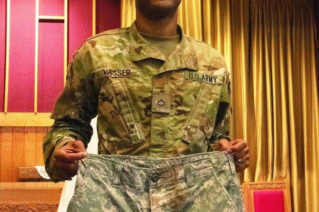 Pvt. 1st Class Eric Vasser, Jr., with 4th Battalion, 39th Infantry Regiment, holds up the pants he was wearing the night he was stabbed by his first wife. Vasser told his story of domestic violence during the 2019 Candlelight Vigil for Domestic Violence Awareness Oct. 9 at the Main Post Chapel. Vasser was stabbed in the leg and abdomen and required two surgeries to repair the damages the stabbing caused. He spoke about the event in hopes to help end the stigma of men speaking out about abuse and to ask others to be vigilant about abuse warning signs and to seek help for those experiencing abuse.
