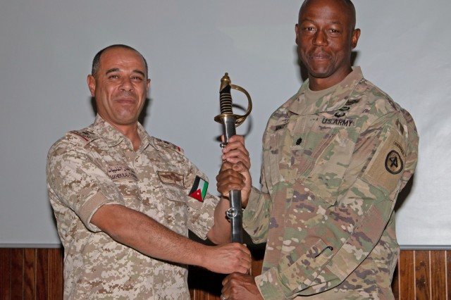 Jordan Armed Forces Lt. Col. Sakher Numan Al Thnabat (left), 7th Mechanized Battalion commander, poses with a sword given as a gift from U.S. Army Lt. Col. Omar Minott, on behalf  of 1st Squadron, 102nd Calvary Regiment, 44th Infantry Brigade Combat Team of the 42nd Infantry in celebration of their Soldier's completion of a Jordan Operational Engagement Program training cycle at Joint Training Center-Jordan October 3, 2019. Jordan and the United States have a strong and enduring partnership in regard to joint training and the JOEP further cements that partnership through persistent training with the Border Guard Forces, Quick Reaction Forces and the 77th Marine Battalion.