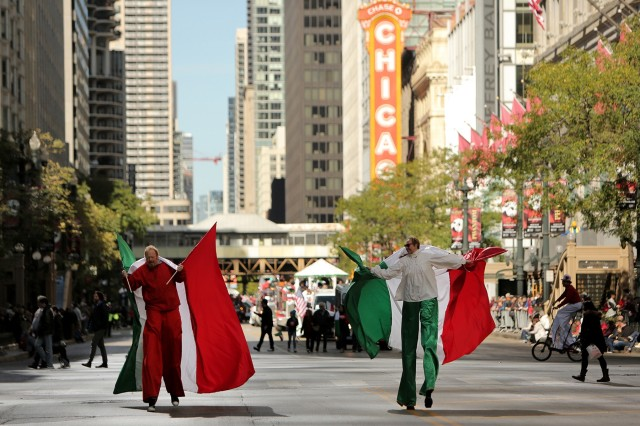 """Parade participants walk on stilts, carrying large Italian flags, during the 2019 67th Annual Columbus Day Parade in the City of Chicago, October 14, 2019. The Joint Civic Committee of Italian Americans sponsored the parade that showcased nearly 110 marching units and floats from various community and ethnic organizations. """"Food and Culture"""" was the theme of this year's parade. One of the newest attractions of this year's parade was the Bersaglieri marching band, a military marching band, which traveled from Sicily to participate in this year's parade. Brig. Gen. Kris A. Belanger, Commanding General, 85th U.S. Army Support Command and parade honorary Grand Marshall, and Capt. Michael J. Ariola, Public Affairs Officer, 85th USARSC, both of Italian-American heritage, participated in the parade and sharing in Italian American culture and contributions to the nation. (U.S. Army Reserve photo by Anthony L. Taylor)"""