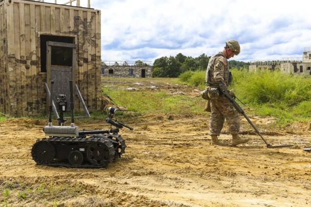 Sgt. 1st Class Joshua Tygret, assigned to 744th Ordnance Disposal Company, 52nd Explosive Ordnance Group, uses a metal detector to safely approach the mission objective during the protection works lane of the fifth annual Department of the Army level explosive ordnance disposal (EOD) Team of the Year competition, Sept. 11 at Fort A.P. Hill, Va. The week-long competition is part of a new initiative of the U.S. Army Ordnance Corps, called the U.S. Army Ordnance Crucible, which combines the results of this competition with two other competitions that were held at Fort Pickett. Those competitions were on ammunition transfer holding points (ATHP) and combat repair teams (CRT). The three unique competitions will provide an opportunity for senior leaders to assess ammunition, maintenance and EOD professionals across the institutional Army, operational force and individual leader development domains. (U.S. Army photo by Staff Sgt. Lance Pounds, 71st Ordnance Group (EOD), Public Affairs)