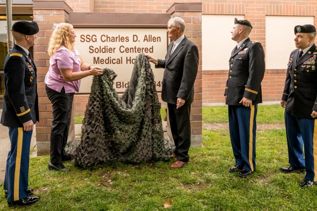 Kathy West and David Allen unveil the sign memorializing their son with the newly designated Staff Sgt. Charles D. Allen Soldier-Centered Medical Home for the 1-2 Stryker Brigade Combat Team as Maj. Aaron Cross, the unit's executive officer, and Madigan Army Medical Center Commander Col. Thomas Bundt and Command Sgt. Maj. Victor Laragione (left to right) look on. The ceremony was held on Joint Base Lewis-McChord, Wash., on Oct. 8. Madigan operates the clinic for the 1-2 SBCT's Soldiers.