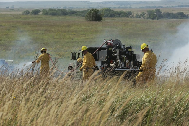 A group of Soldiers and Airmen from the Kansas National Guard spray down flames with water from a High Mobility Multipurpose Wheeled Vehicle (HMMWV) during an integrated exercise between Guard members and civilian fire departments at the Smokey Hill Range in Salina, Kansas, Sept. 19. The HMMWV's can hold anywhere from 200 to 400 gallons of water and has 300 feet of hoses to provide to a fire fighting effort.