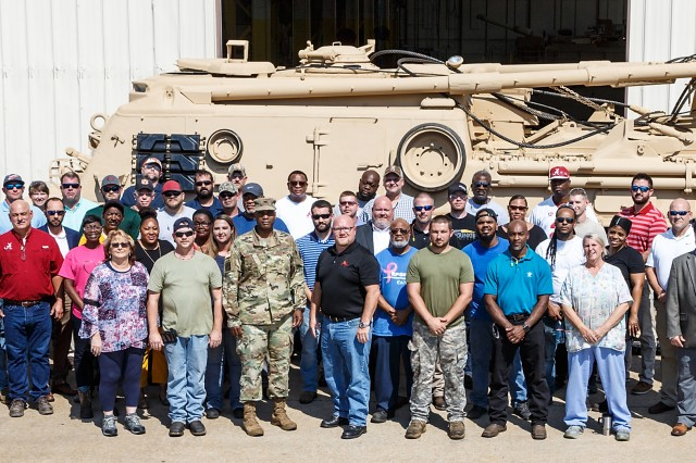 Anniston Army Depot employees who assisted in overhauling 10 M88 recovery vehicles for the Kingdom of Saudi Arabia stand beside one of the vehicles.