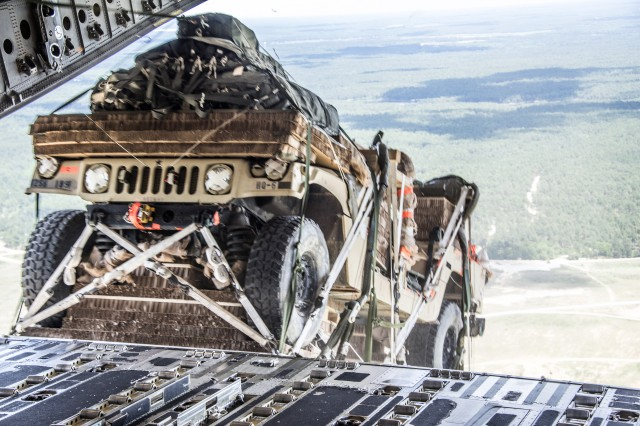 An M997 High Mobility Multipurpose Wheeled Vehicle (HMMWV) is airdropped using gravity release method during the Advanced Low Velocity Airdrop System -- Dual Row Airdrop System - ALVADS-DRAS - Follow-on Test and Evaluation (FOT&E) from a U.S. Air Force C-17 aircraft.