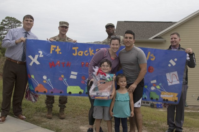 """Tristan Jenkins stands with his mother Courtney Jenkins, father Staff Sgt. Timothy Jenkins, sister Divina, Fort Jackson Garrison Commander Col. John """"Wes"""" Hankins and Command Sgt. Maj. Anthony J. Wilson, and C.C. Pinckney faculty members as he is awarded a prize during the annual Math Prize Patrol. Tristan and his Family pledged to solve math problems together that allowed them to be entered into the contest."""