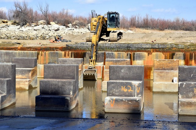 JOHN MARTIN RESERVOIR, Colo. -- The contractor uses an excavator to remove equipment from the stilling basin, March 25, 2019. Baffle blocks are visible on the left.