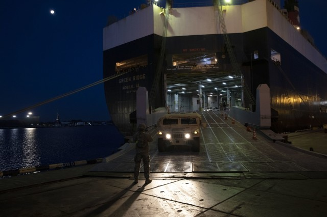 A U.S. Army Soldier ground guides a Humvee down the ramp of the Green Ridge, a carrier ship, at the Port of Riga, Latvia, Oct. 16, 2019. Active duty Soldiers and reservists from the 21st Theater Sustainment Command, the 598th Transportation Brigade and various movement control teams conducted 24-hour operations at the port to offload and stage over 300 pieces of equipment, the largest shipment of U.S. Army equipment to come through a port in the Baltic Region (U.S. Army photo by Sgt. Erica Earl, 5th Mobile Public Affairs Detachment)