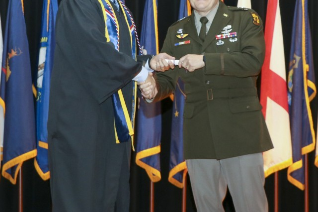 Maj. Gen. John R. Evans, Jr, Commanding General, Fort Knox and U.S. Army Cadet Command, hands Staff Sgt. Noel Gerig, 1st Theater Sustainment Command (TSC), a diploma during the Fort Knox Army Education Center College Graduation Ceremony at Waybur Theater, Oct, 17, 2019 on Fort Knox, Ky. (U.S. Army photo by Spc. Zoran Raduka)