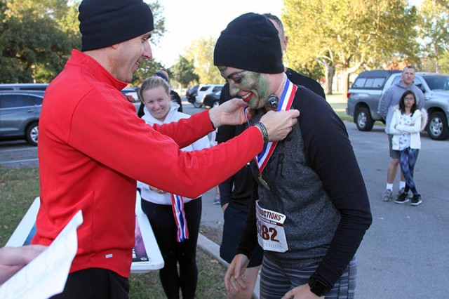 Col. Michael Konczey, 434th FA Brigade commander, places a medal on Cassie Steiner (who dressed as Frankensteiner). Steiner won her division with a time of 25 minutes, 53 seconds.