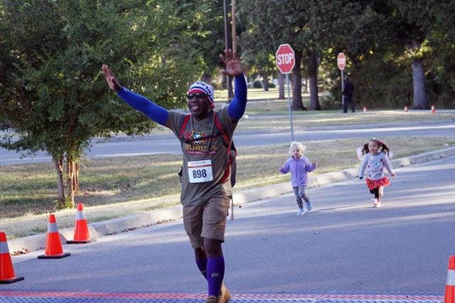 Guy Eugene, dressed as a ruck marcher, crosses the finish line with children approaching closed behind him during the Monster Dash.