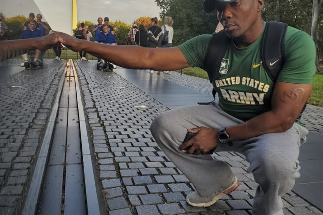 Lt. Col. Frederick Moss, a senior staff officer for the U.S. Army Reserve Headquarters at Fort Bragg, North Carolina, visits the Vietnam Veterans Memorial Wall with his family in Washington, D.C., Oct. 12, 2019. Moss runs multiple military races each year - including the Army Ten Miler in Washington, D.C. - while carrying a binder holding the names of the fallen Vietnam War service members. Moss decided to print the binder and run with it in honor of his father, Terry Leon Williams, who is a Vietnam veteran who survived the war, but who lost comrades in combat. Moss recognized that his father's generation of veterans were rarely welcomed with open arms after they returned from war. His desire to run with the binder is an effort to bring remembrance to their legacy.