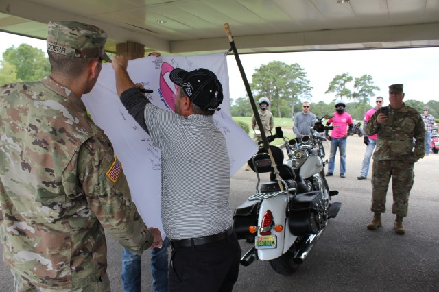 A person whose life was affected by breast cancer signs the pink ribbon flag at the formation's first stop, Silver Wings Golf Course.