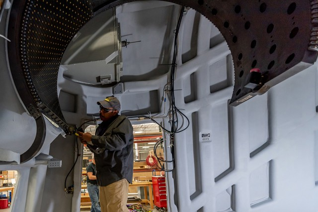 Sheet Metal Mechanic Peter Tom-Wing installs the gun port shield guide rails on a Navy weather shield. Tom-Wing is assigned to the Systems Integration and Support Directorate's Electronics Shelter System Branch.
