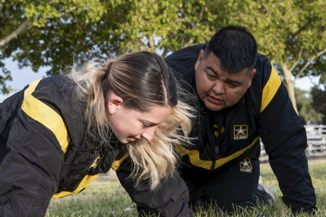 Army Reserve Spc. Shaylene Quigley (left), a carpentry and masonry specialist with the 333rd Engineer Detachment (Utilities), performs the push-up portion of her annual physical fitness test while being coached by Sgt. Brandon Begay at Kirtland Air Force Base, Albuquerque, New Mexico, October 20, 2019. (Army photo by Staff Sgt. David Overson)