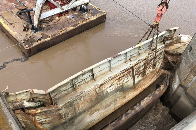 Salvagers lift a sunken barge from the water upstream of Webbers Falls Lock & Dam 16 near Webbers Falls Oklahoma, on August 27, 2019. Two barges slammed into Webbers Falls Lock & Dam 16 on the McClellan-Kerr Arkansas River Navigation System during a near record flood event in May 2019.