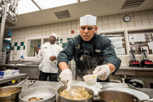 Sgt. 1st Class Francisco Delgado spoons out a measured amount of one of his creations during a plant-based cook-off Oct. 16, 2019, with Spc. Trevor Gillespie at the Guns and Rockets Dining Facility on Fort Sill, Okla. Delgado, the DFAC manager, accepted Gillespie's challenge and made a one-course meal whereas Gillespie created a three-course meal.