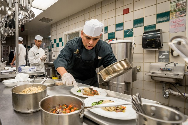 Sgt. 1st Class Francisco Delgado makes the finishing touches of his meal presentation during the plant-based cook-off at the Guns and Rockets Dining Facility on Fort Sill, Okla., Oct. 16, 2019. The dining facility offers plant-based entrees and other fare to about 350 diners the staff feeds each day.
