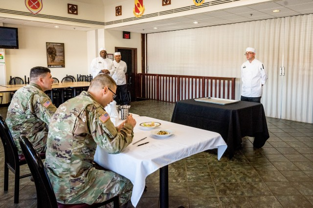 Spc. Trevor Gillespie receives feedback about his culinary creations during the first plant-based cook-off at the Guns and Rockets Dining Facility on Fort Sill, Okla., Oct. 16, 2019. Gillespie learned his plant-based skills from Sgt. 1st Class Francisco Delgado and will take that knowledge and skills to his next duty assignment soon.