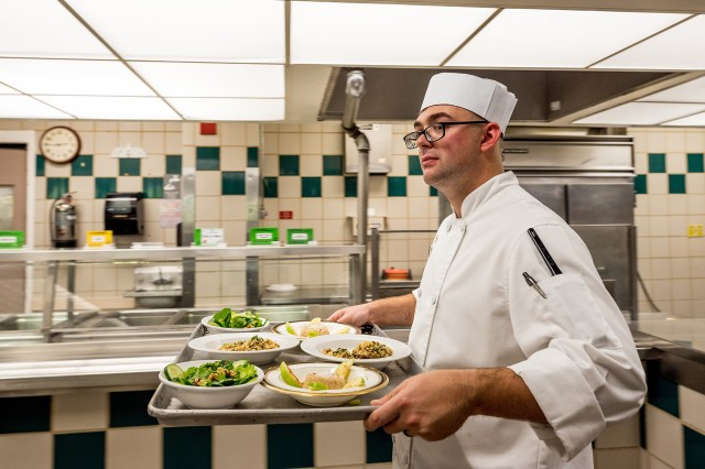 Spc. Trevor Gillespie carries his three-course meal to the judges during the first plant-based cook-off at the Guns and Rockets Dining Facility on Fort Sill, Okla., Oct. 16, 2019. Gillespie's table fare impressed the judges, but not quite enough as his mentor, Sgt. 1st Class Francisco Delgado won the competition by a single point.
