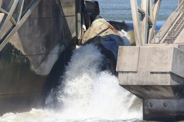 Water flows uncontrolled around a sunken barge on the water upstream side of Webbers Falls Lock & Dam 16 near Webbers Falls Oklahoma, on August 20, 2019. Two barges slammed into Webbers Falls Lock & Dam 16 on the McClellan-Kerr Arkansas River Navigation System during a near record flood event in May 2019. (U.S. Army photo by Preston L. Chasteen/Released)