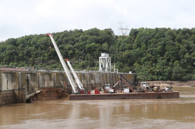 Salvagers lift a sunken barge from the water upstream of Webbers Falls Lock & Dam 16 near Webbers Falls Oklahoma, on August 27, 2019. Two barges slammed into Webbers Falls Lock & Dam 16 on the McClellan-Kerr Arkansas River Navigation System during a near record flood event in May 2019. (U.S. Army photo by Stacey Reese/Released)