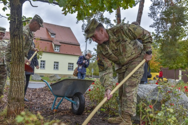 U.S. Army Brig. Gen. Christopher Norrie, commander of 7th Army Training Command, (7 ATC) and Command Sgt. Maj. Franklin Velez, senior enlisted advisor for 7th ATC, help plant an oak tree with community members outside the 7 ATC headquarters, Tower Barracks, Grafenwhoehr, Germany Oct. 8, 2019. The Oak tree is the national tree for both Germany and the United States and stands for the symbiotic relationship between the local and military communities. (U.S. Army photo by Sgt. Christopher Stewart)