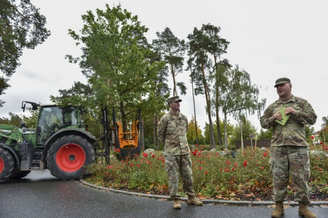 U.S. Army Col. Timothy Davis, the G3 for 7th Army Training Command (7 ATC) speaks to an audience as Lt. Col. Timothy Maracle, chaplain for 7 ATC, looks on during an Oak tree planting ceremony at the 7 ATC headquarters, Tower Barracks, Grafenwhoehr, Germany Oct. 8, 2019. The Oak tree is the national tree for both Germany and the United States and stands for the symbiotic relationship between the local and military communities. (U.S. Army photo by Sgt. Christopher Stewart)