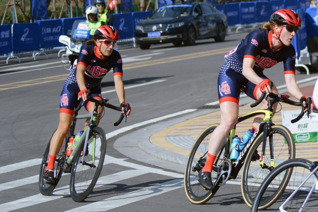 Navy Cdr. Kathleen Giles, right, and Air Force Lt. Col. Melissa Tallent round the first corner in the second lap of the 50-mile cycle road race in the CISM Military World Games in Wuhan, China, Oct. 20, 2019.