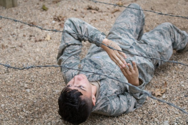 Air Force JROTC Cadet Kaiden Koso of Blue Springs South High School remains vigilant as he crawls under barbed wire at the Physical Endurance Course.