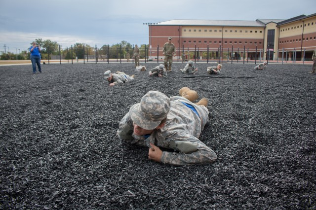 Moberly High School JROTC cadets crawl on a rubber turf pit between sets of sprints and pullups.